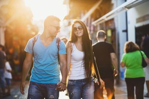 A young couple walking down a sunny street in a city