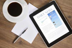 Tablet showing news on desk