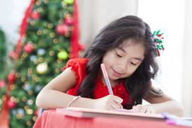 girl doing work in front of a Christmas tree