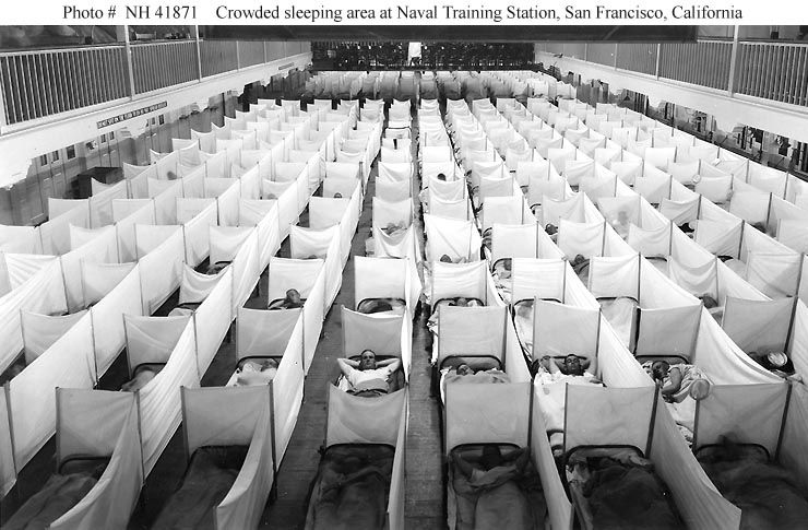 A picture of a crowded sleeping area, with beds separated by sneeze screens.