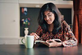 Girl reading book next to a coffee mug