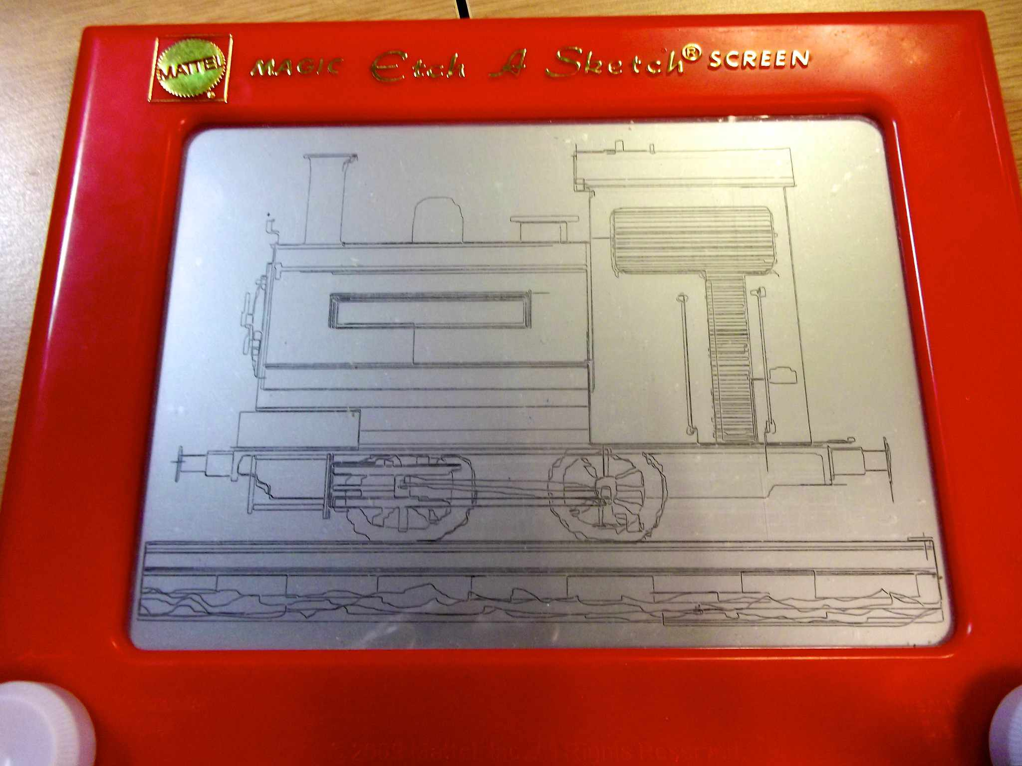 Image of an Etch-a-Sketch with a train drawn on it.