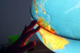 A child's hand runs along the equatorial seam of an illuminated globe