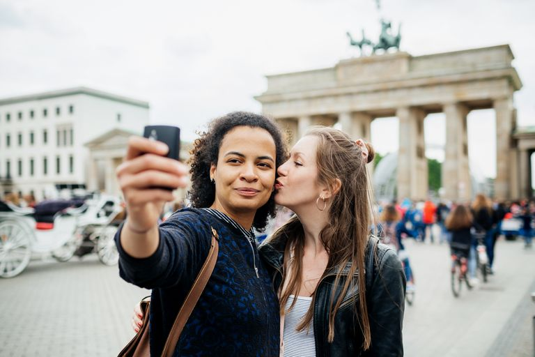 Young lesbian Couple Stop To Take A Selfie At Brandenburg Gate in Berlin