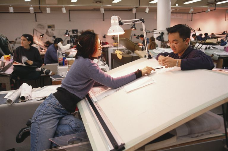 architecture school studio area, drafting tables, students working together on projects