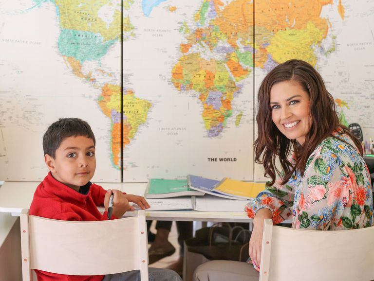 Maestra y niño de primaria en salón de escuela