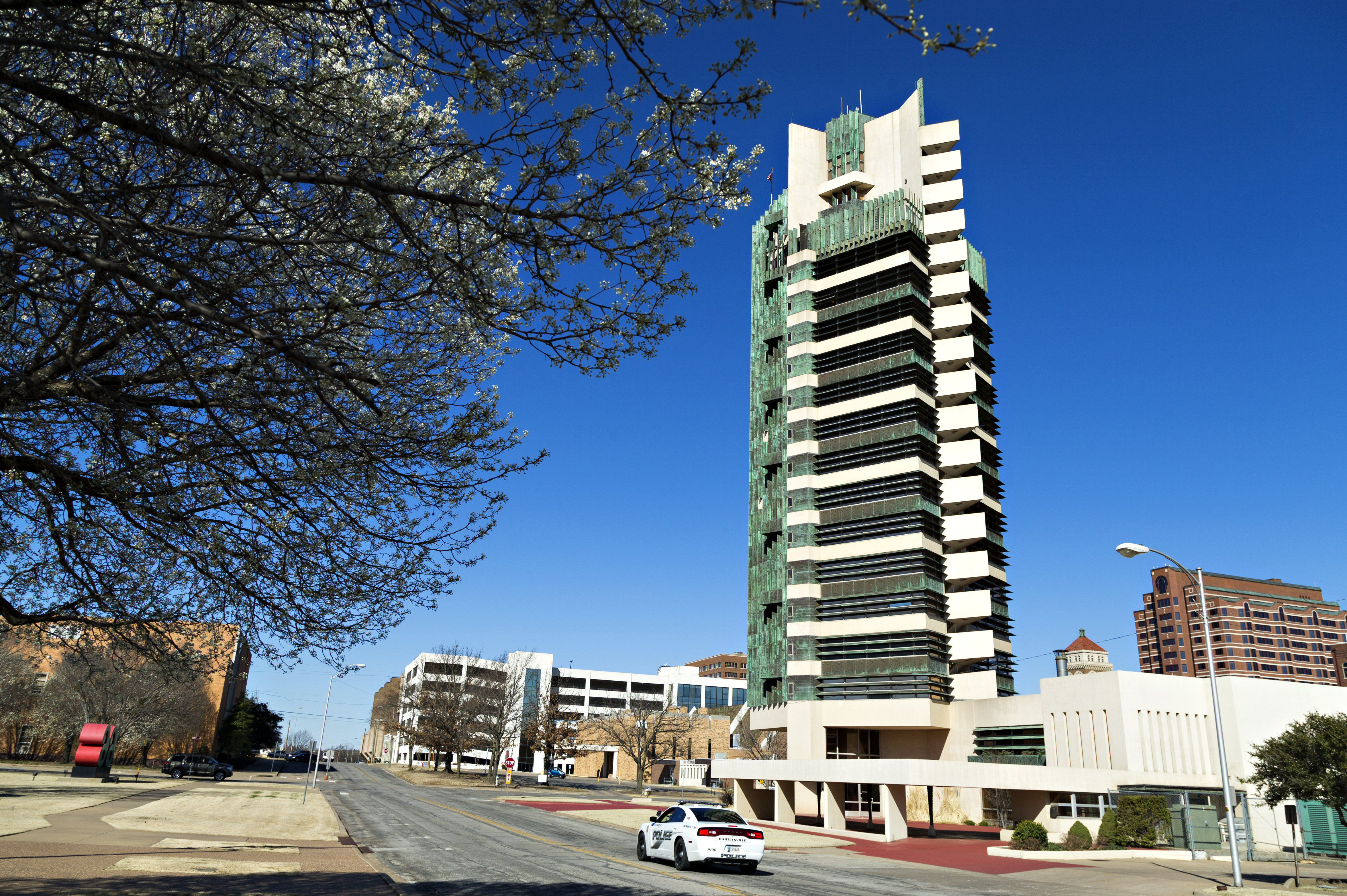 A spectacular tower building, multiple stories of copper and concrete in the downtown area of a very small city in Oklahoma.