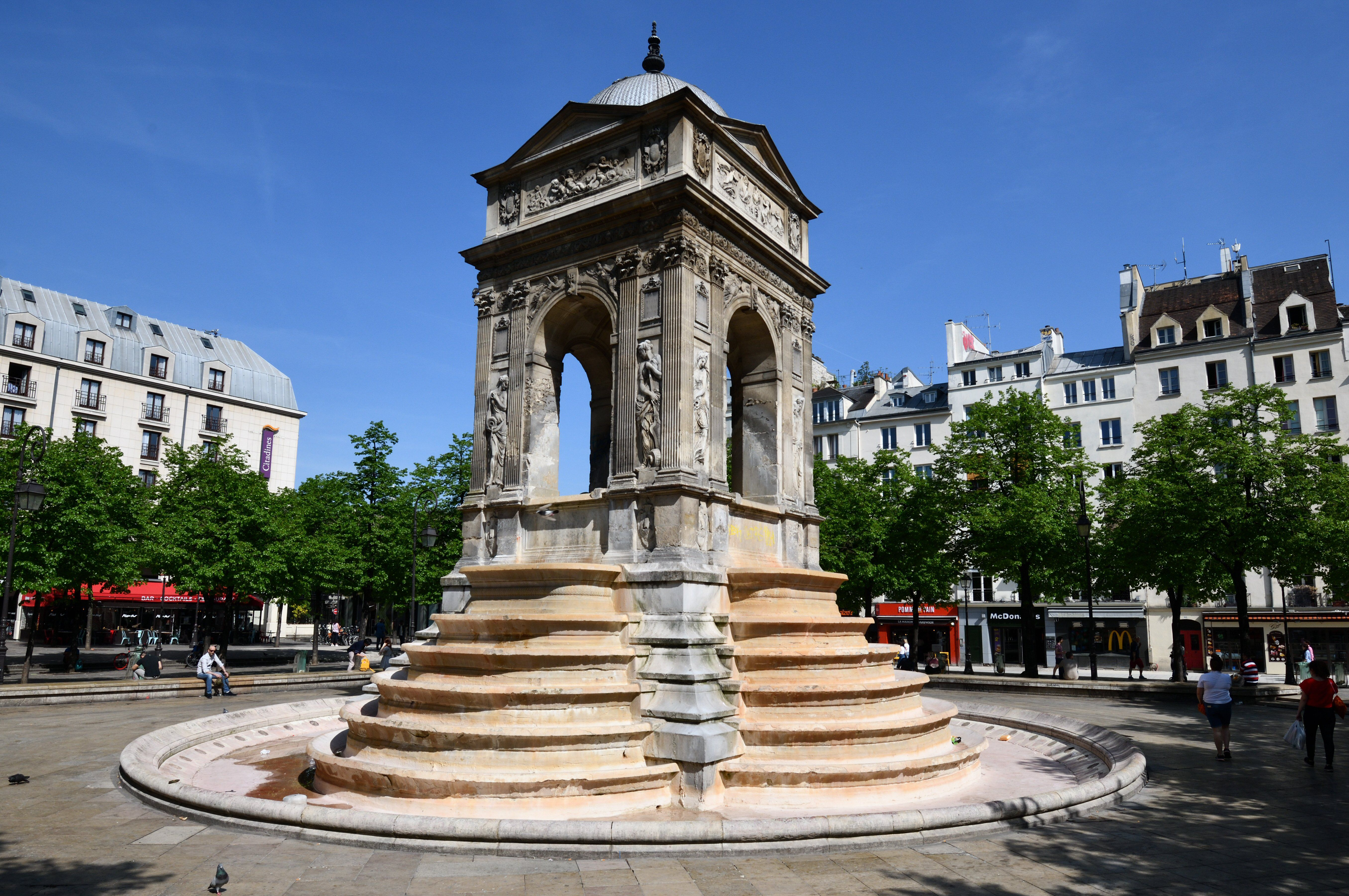 four-sided open monument with six steps on each side leading up to where a fountain or bell would be
