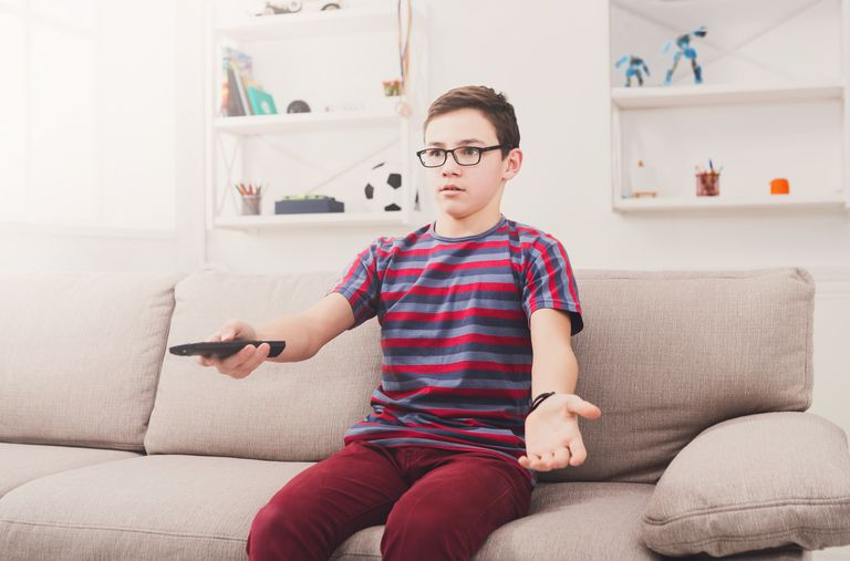 Teenager boy watching television, using remote control