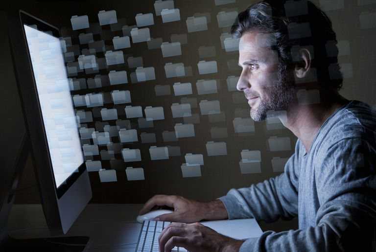 Man sitting in front of computer screen at night