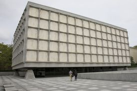 rectangular box of a building five squares high and 15 squares across seemingly sitting on corner concrete pyramids with a flat roof