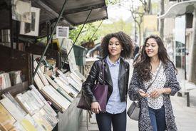 Two women walking past a bookshop