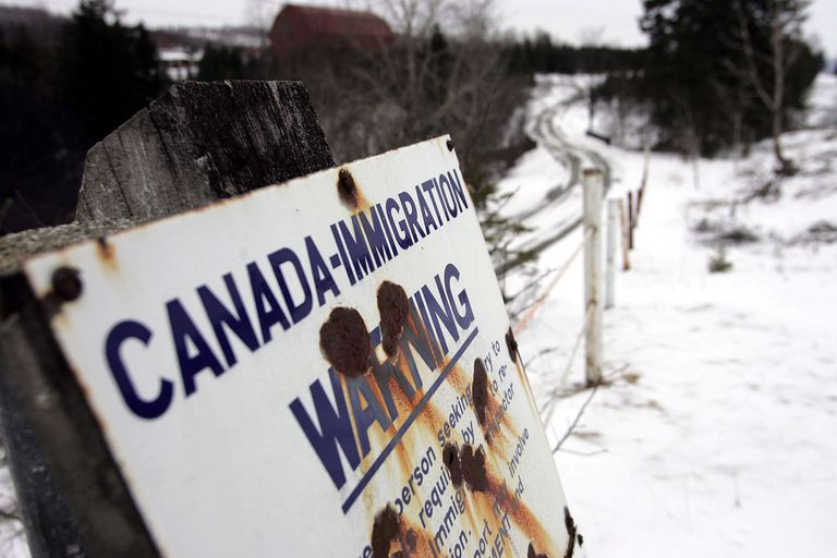 Sign along US – Canada border warns of Canadian immigration laws