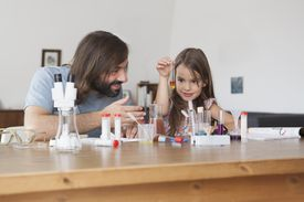 Father and daughter doing science experiment at home