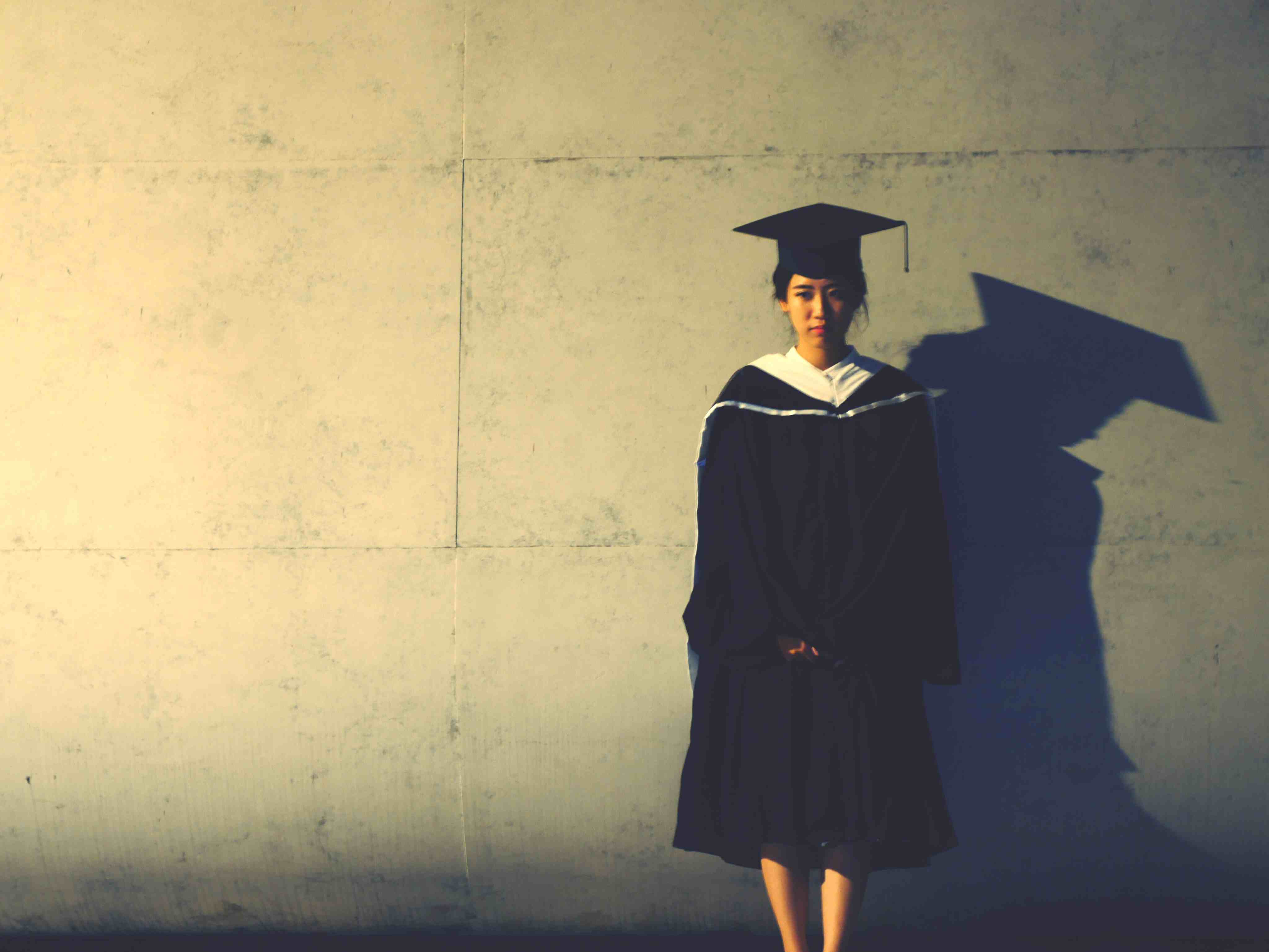 Portrait Of Woman In Graduation Gown Standing Against Wall