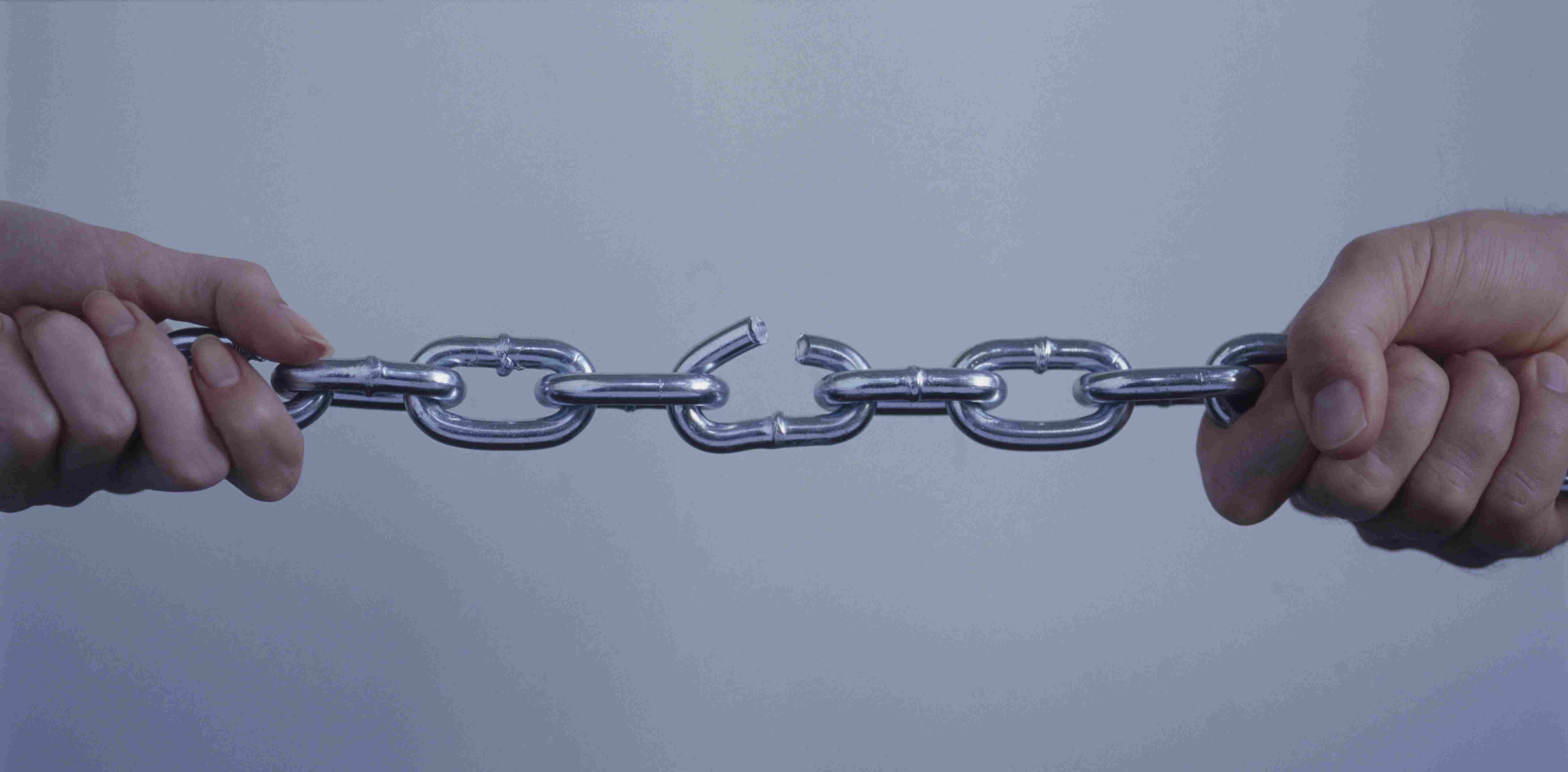 Hands pulling on chain with broken link