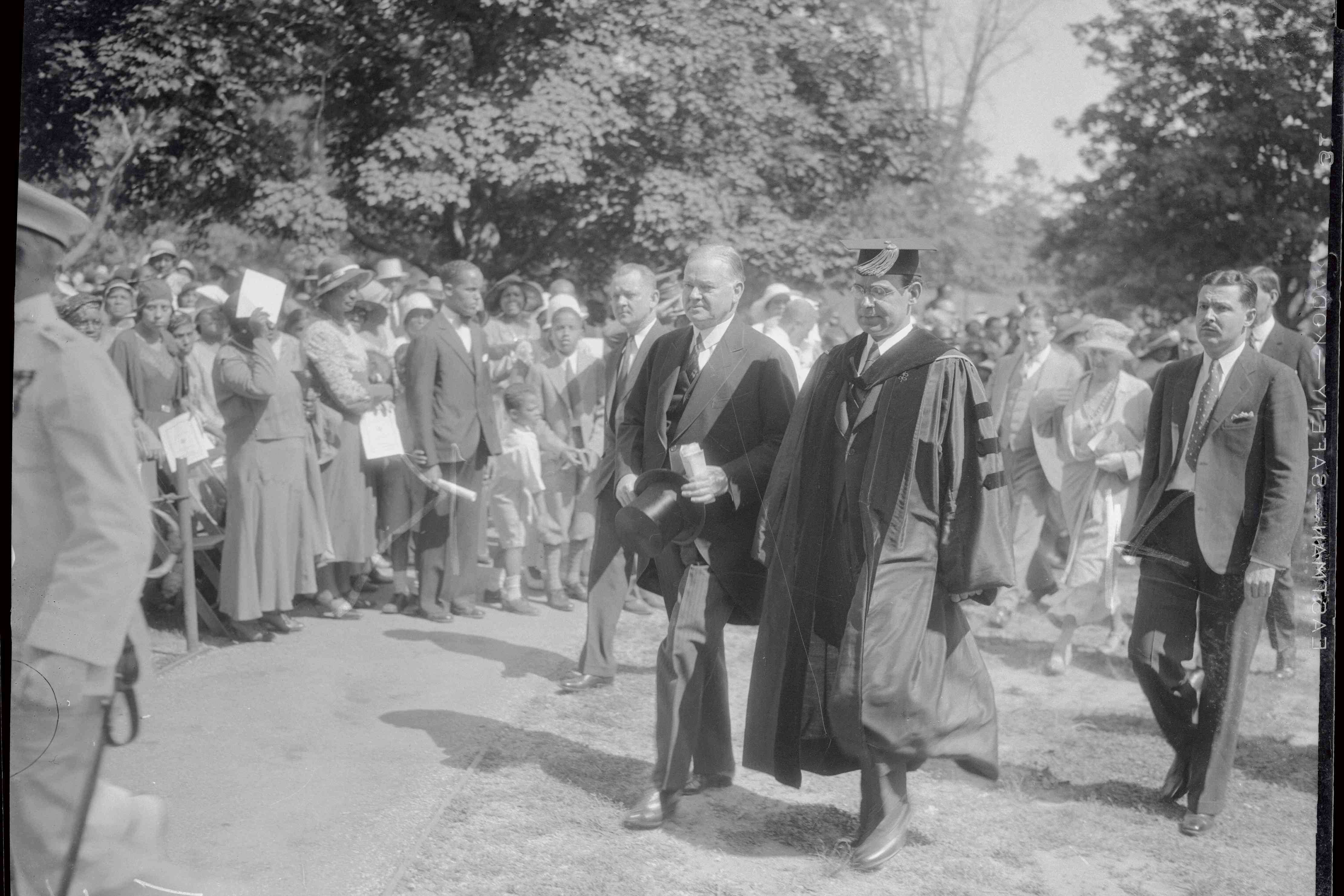 Dr. Mordecai Johnson wears graduation robe and cap while walking with President