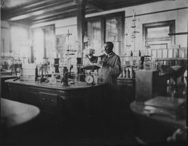 Black and white photo of George Washington Carver working in his lab.
