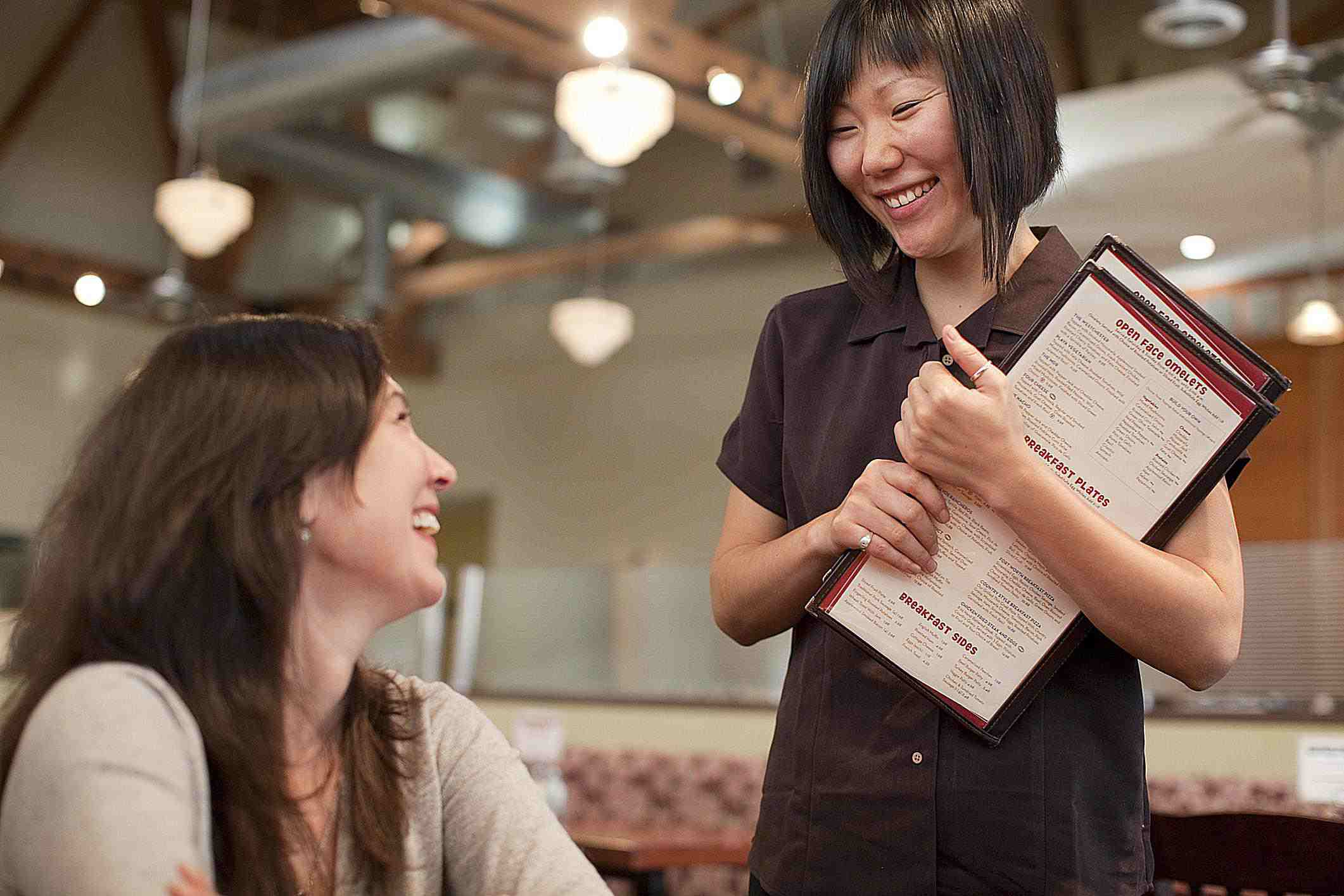 A waitress with menus in hand talking to a customer.