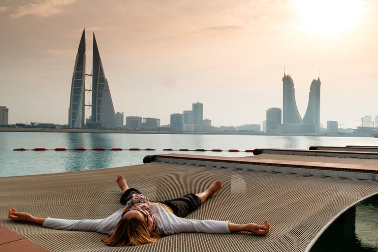 A person is sprawled out on a net at Pier Against Sky overlooking a Bahrain cityscape
