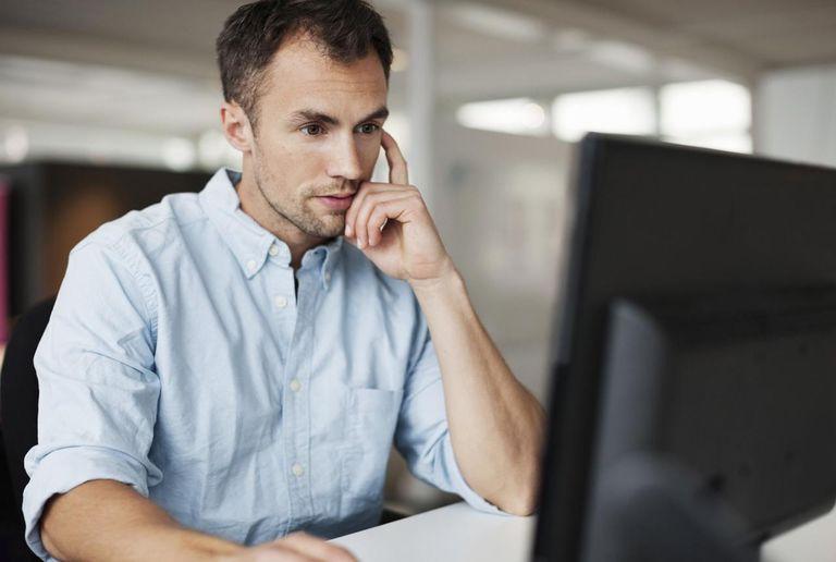 Man using desktop PC at desk in office