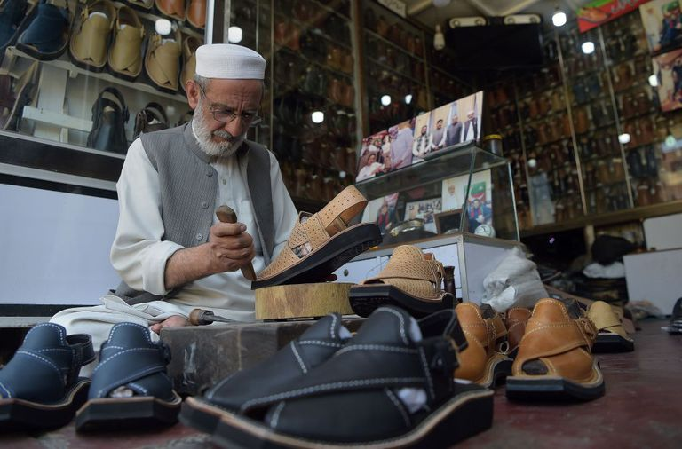 man making string shoes