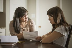 Mother and daughter looking at a note
