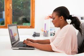 Picture of a woman working on her laptop at her desk