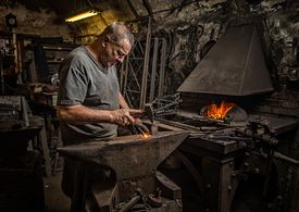 Black smith working on anvil next to smelter