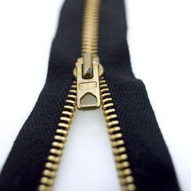 Close up of half unzipped black zipper against white background.