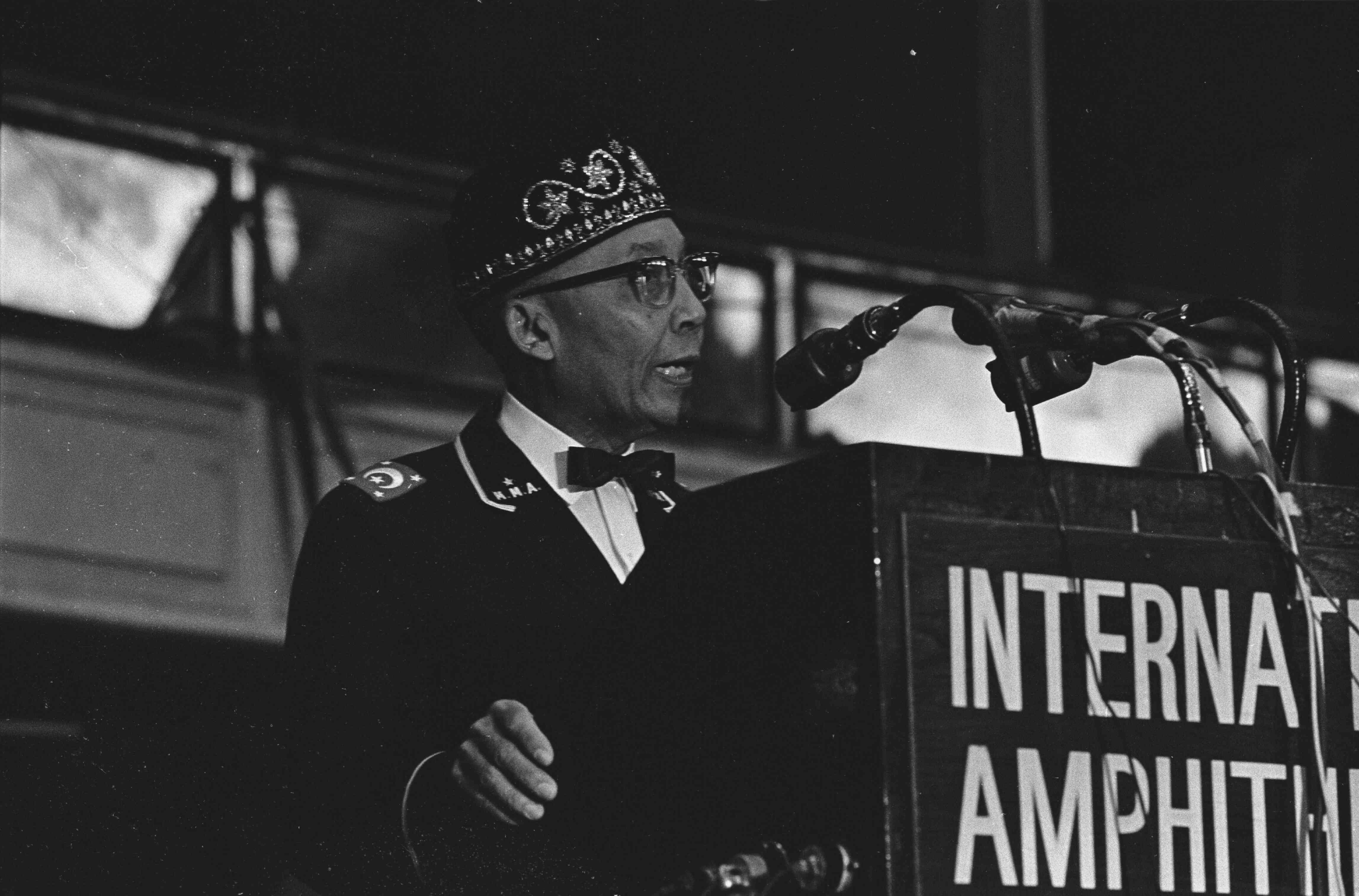 Elijah Muhammad standing at a podium and speaking into a microphone
