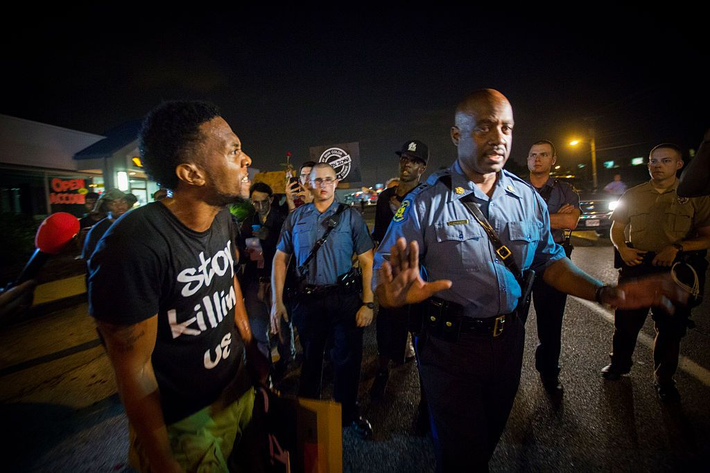 Missouri State Trooper Captain Ronald Johnson gets an ear full from a protester