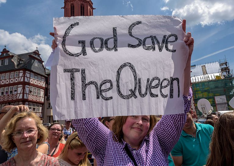 "Woman holding sign reading ""God Save the Queen"""