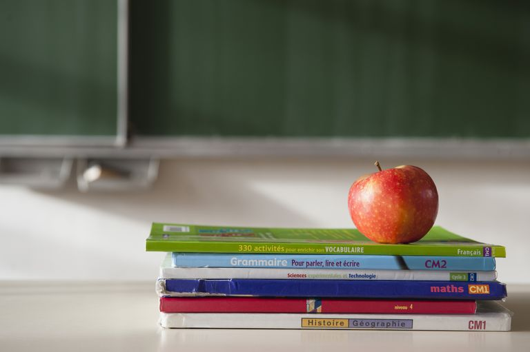 apple on top of stacked french books in a classroom