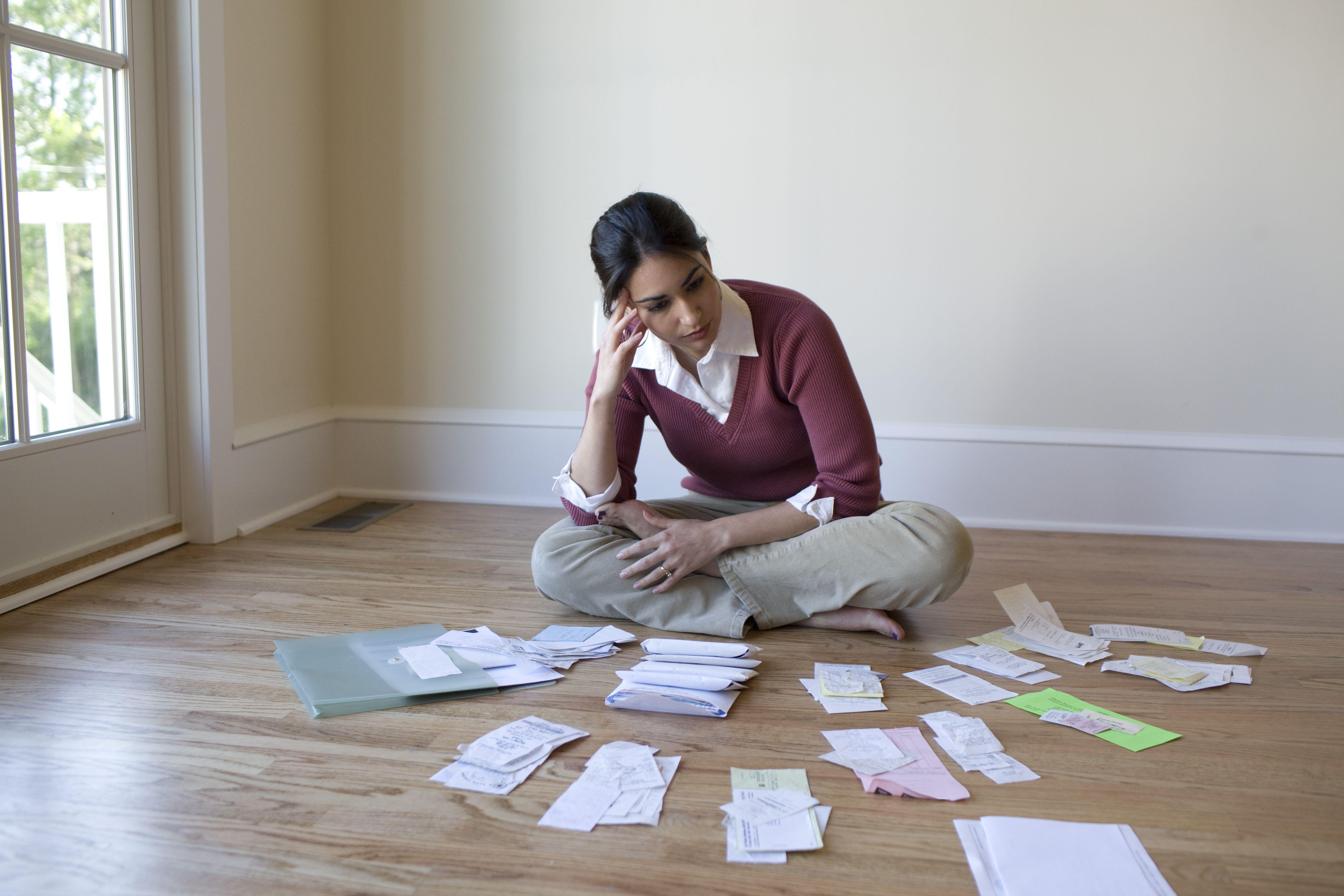 Muchacha sentada en el suelo preocupada ante facturas y recibos