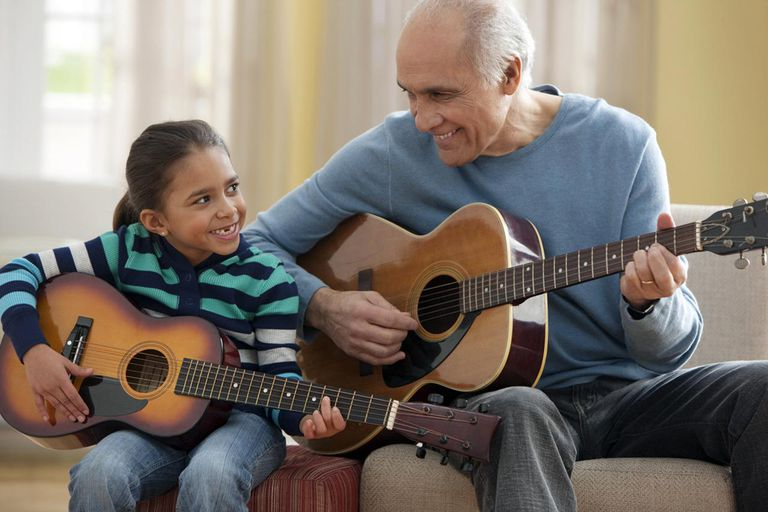 Grandfather teaching granddaughter how to play guitar.