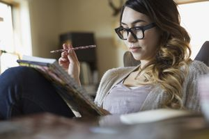 Picture of a woman with glasses writing in a notebook