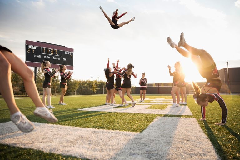 Teenage girls high school cheerleading team performing double nine jump on sunny football field