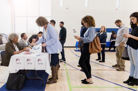 As they wait in a long line, a group of voters study their smartphones.