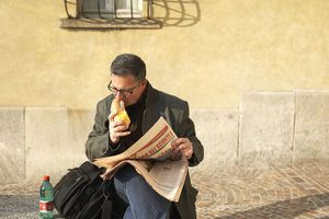Italian man eating and reading newspaper