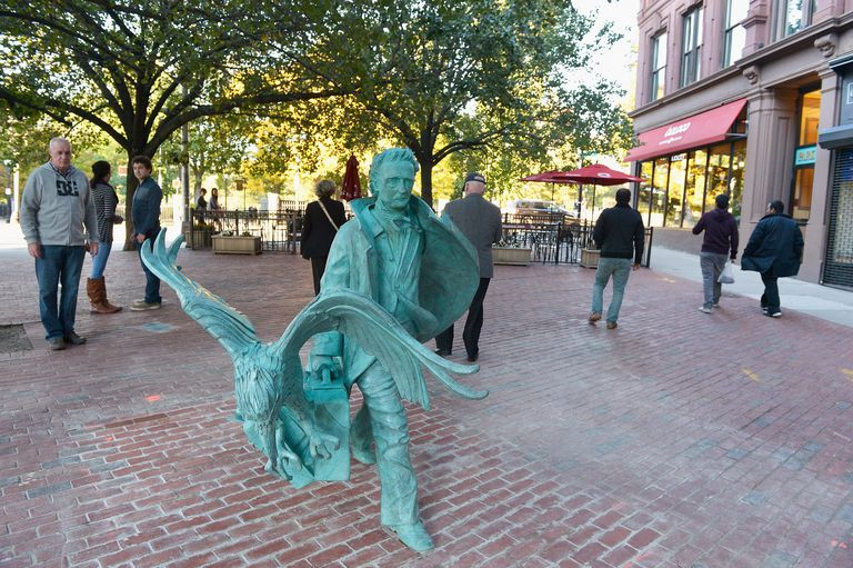 A statue of Edgar Allen Poe with a raven, which is located in an outdoor plaza near Boston Common.