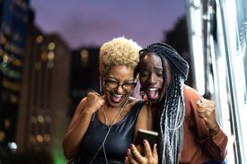 Multi-Ethnic Friends Celebrating Good News on Mobile