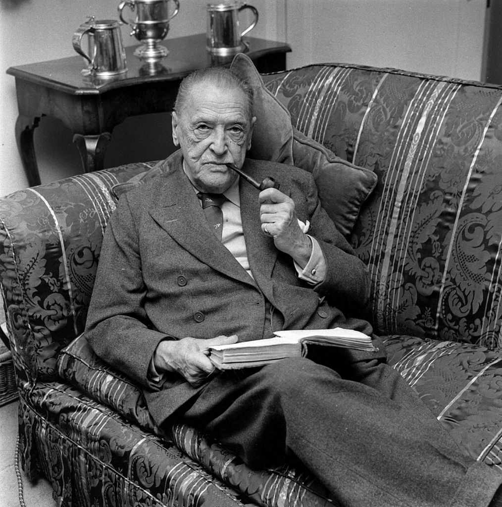 W Somerset Maugham seated on sofa with pipe