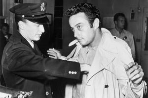 Photograph of comedian Lenny Bruce being searched by a policeman.