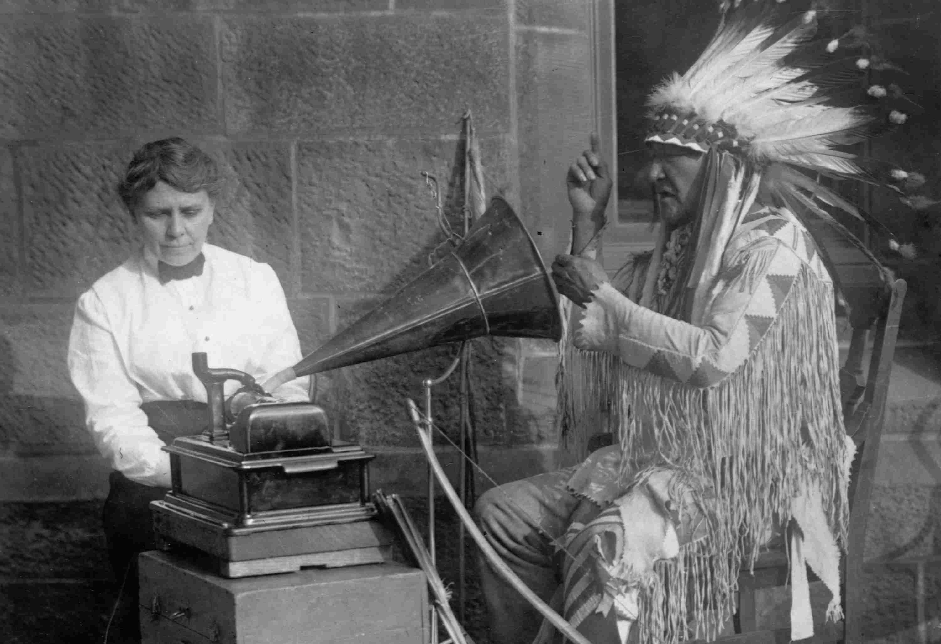Photograph of Native American being recorded by a phonograph.