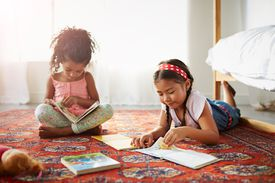 Two sisters reading books on the floor in bedroom.