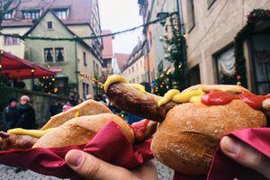 Eating bratwurst at Christmas market, Bavaria, Germany
