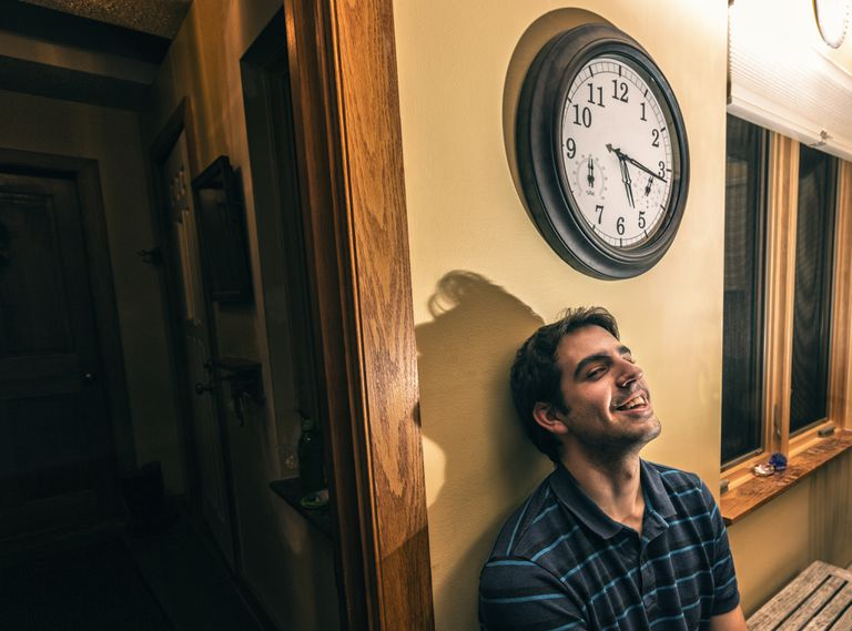 Sideways Smiling Young Man Sitting Waiting Under Wall Clock