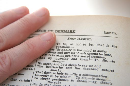 Fingers on top of the text of Hamlet