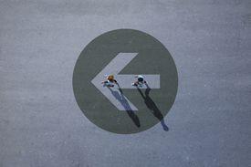 Top view of two people walking across asphalt with big painted arrow